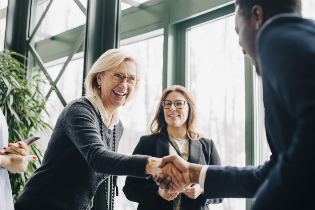 Business people shaking hands, smiling, deal