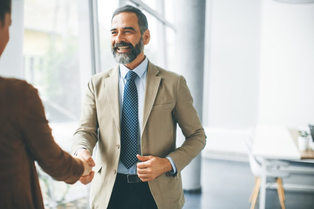 Senior businessman handshaking with young woman in the office