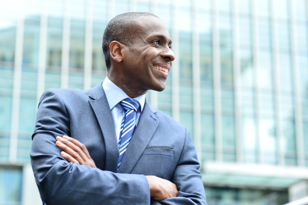 Happy businessman in suit keeping arms crossed